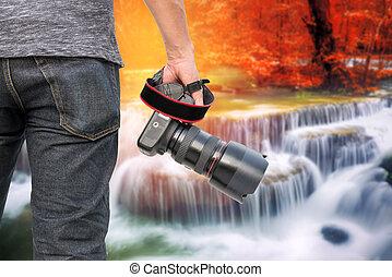 Photographer with Waterfall in deep forest at huay mae ka min of Karnjanaburi in Thailand