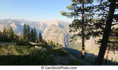 Photographer woman shooting panorama at Washburn Point in Yosemite National Park, California, United States. View of Half Dome, Liberty Cap, Yosemite Valley, Vernal Fall, and Nevada Fall.