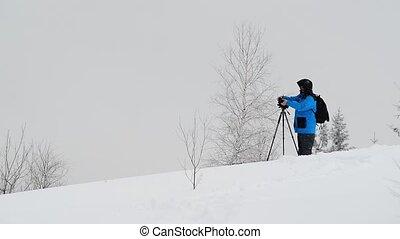 Photographer work in winter mountain - Photographer take a...