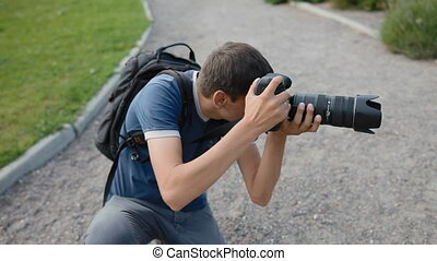 Male photographer work outdoor. He hold a camera with big telephoto lens.