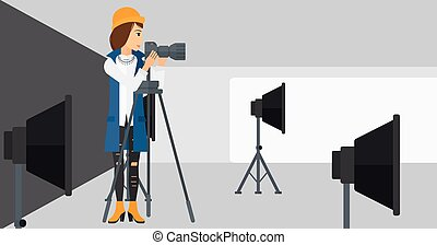 Photographer working with camera on a tripod. - A ...