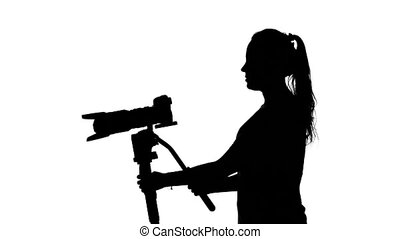 Photographer works with a large lens. White. Silhouette