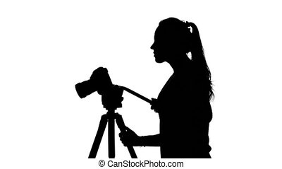 Photographer works with a tripod. White. Silhouette