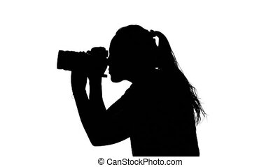 Photographer works with the camera in the studio. White. Silhouette