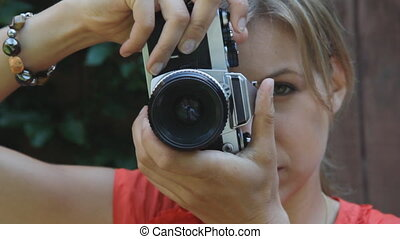 Young woman takes a photograph with a retro 35mm film camera.
