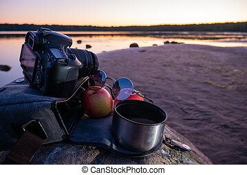 Photographer's bag with 2 apples and coffee.
