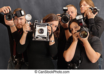 Photo of paparazzi waiting for the right moment to take photos. Focus on the two females in front.
