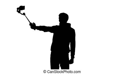 Photographer's silhouette making selfie with help of...
