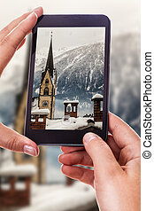 Photographing an austrian town - a woman using a smart phone...