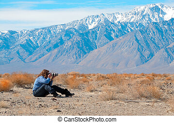 Photographer getting landscape shots of the mountains and desert at Death Vallley in California, USA.