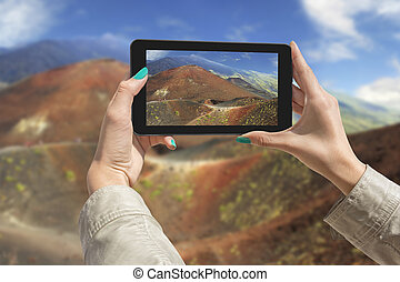 Photographing Etna volcano with tablet - Girl taking...