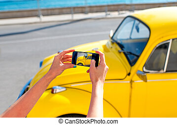 Woman photographing with smart phone old yellow car on the street
