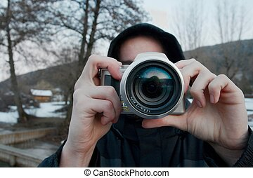 Photographing - Person photographing outdoors with a compact...