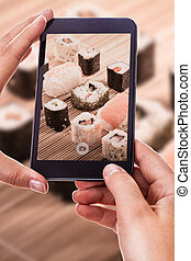 a woman using a smart phone to take a photo of some delicious sushi rolls