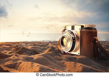 Photographs on holiday - Vintage photo camera on the sand at...