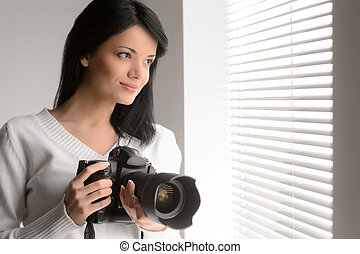 Photography is her hobby. Portrait of beautiful young woman holding a camera and looking through the window