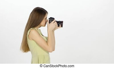 Beautiful young model makes photo, girl with long hair and bright dress stands in profile, model holds a camera and presses her finger on the button, on white background