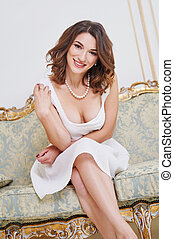 Photos of beautiful sensual woman in white dredd sitting on a sofa