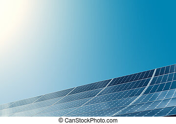 Photovoltaic modules of huge solar panels with clear sky and sun on background