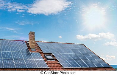 Photovoltaic or solar panels on roof against blue sky.