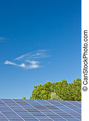 Photovoltaic panels in a solar power plant over a deep blue...