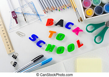 """Phrase """"Back to school"""" from multi-colored plastic letters on a white background with school articles."""