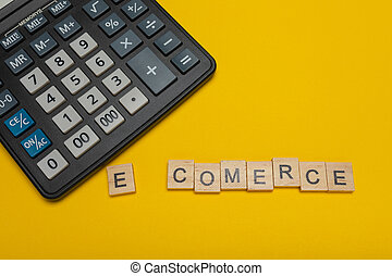 Phrase or word - e-comerce. Wooden block letter word and modern calculator on a yellow background, business concept with space for text