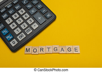 Phrase or word - mortgage. Wooden block letter word and modern calculator on a yellow background, business concept with space for text