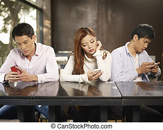 young people playing with smartphones and ignoring each other.