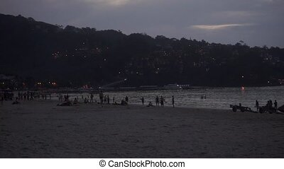 Phuket Patong beach in the evening with silhouettes of people