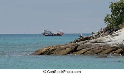 PHUKET, THAILAND - November 18, 2012. Men fishing on the shore. Fishing boat swaying on the waves.