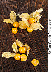 Physalis. - Physalis, groundcherriesl on brown textured aged...
