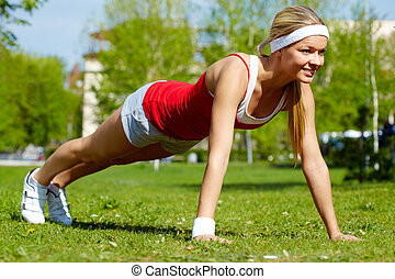 Physical exercise - Portrait of a young woman doing physical...