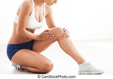 Physical injury. Cropped image of beautiful young woman in sports clothing touching her injured knee while kneeling on the floor