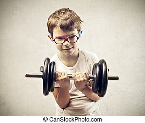 physical strength - small child with weights in hand on gray...
