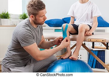 Physical therapist applying medical tape - Physical...