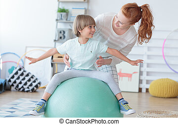 Physical therapist assisting little boy sitting on gym ball ...