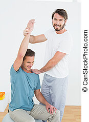 Physical therapist assisting man wi