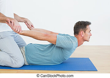 Physical therapist assisting man wi - Side view of a...