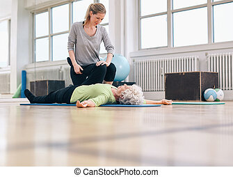 Physical therapist assisting senior woman with leg exercise