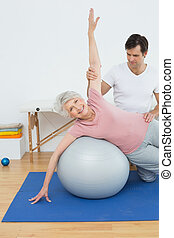 Physical therapist assisting senior woman with yoga ball