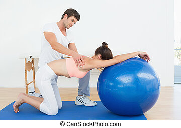 Physical therapist assisting woman with yoga ball
