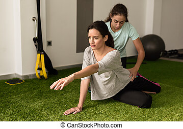 Physical therapist assisting young caucasian woman with...