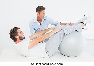Physical therapist assisting young man do sit ups in the gym...