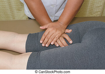 Physical therapist doing massage on woman's leg