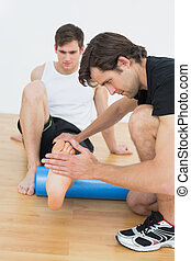 Physical therapist examining a young mans leg at the ...