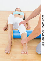 Physical therapist examining a young woman's leg
