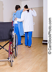 physiotherapist helping patient to walk without wheelchair in hospital room