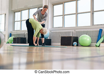 Physical therapist helping senior woman at gym