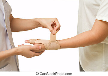 Physical therapist helps woman's patient wearing a wrist  brace